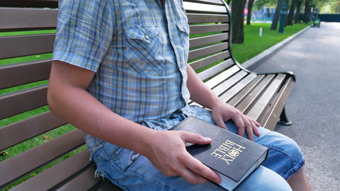 Man is holding Holy Bible in his hand sitting on a bench in a park in the summer GIF