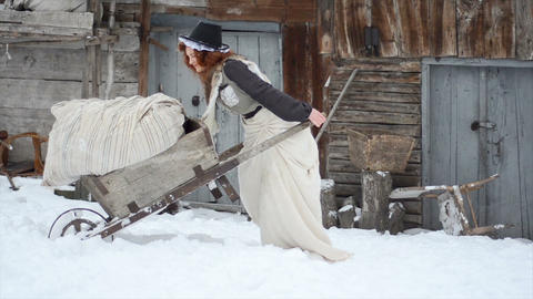 Charming red-haired girl carries a heavy cart in the winter. Hardworking Footage