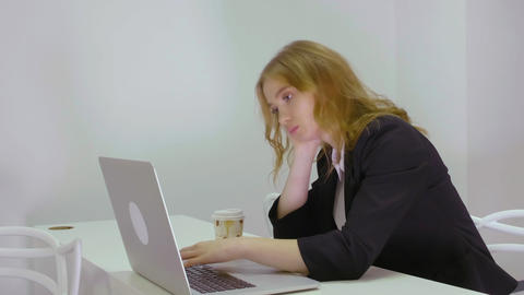 Tired business woman at table working on notebook computer in business office Live Action