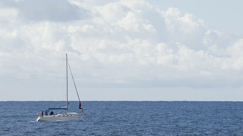 Boat with furled sails sailing across blue sea under cloudy sky, recreation Live Action