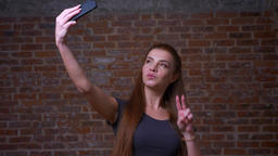 Cute caucasian female is taking selfie and showing her two fingers on her phone Footage
