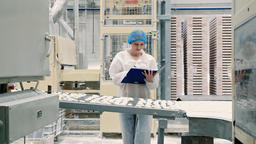 Controller checking conveyor with candies. Candy factory Live Action