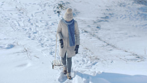 Frozen funny woman dragging sledge outdoor Footage