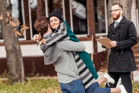 Happy couple embracing after buying new own house, celebrating relocation Photo