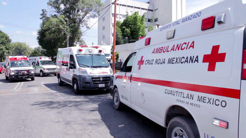 Some red cross ambulances outside a hospital Footage