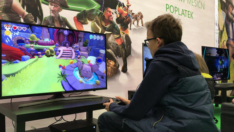 Child playing XBox game in gaming section of family festival Live Action