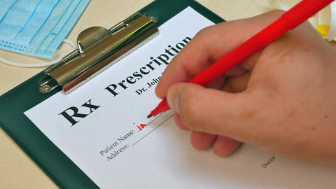 Doctor hand writing rx prescription Live Action