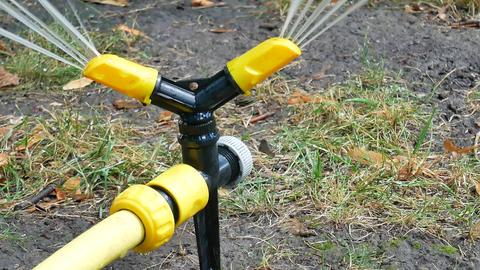 Yellow black watering lawn sprinkler system sprays water Footage