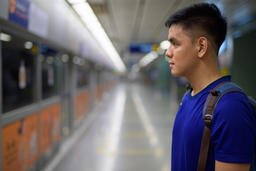 Young Asian tourist man waiting for the train at the subway station Photo