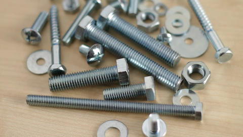 Rotating bolts and nuts on workbench Stock Video Footage