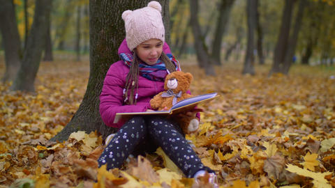 Cute girl reading book under the tree in autumn park 영상물