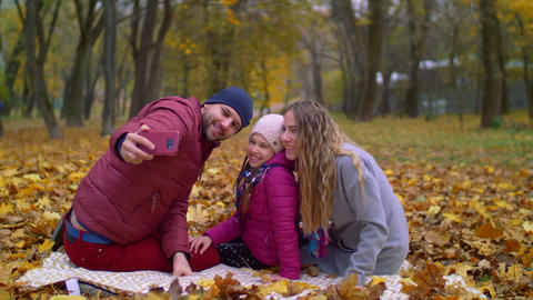 Positive family taking selfie on cellphone in autumn Footage
