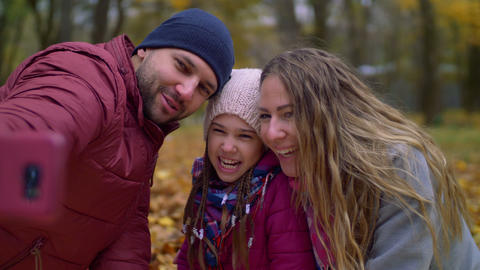 Carefree family making selfie photo in autumn nature GIF