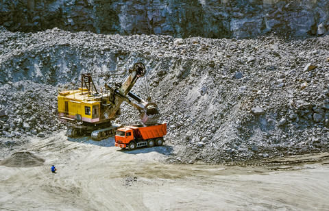 huge excavator, truck and man standing next on granite quarry Photo