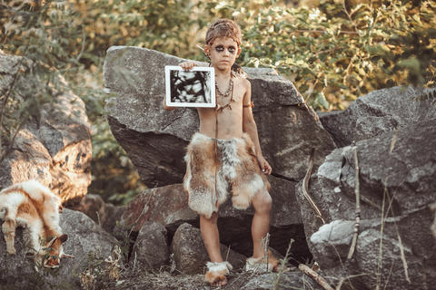 Caveman, manly boy making holding tablet PC Photo