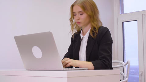 Serious young businesswoman working on laptop at workplace in office Live Action