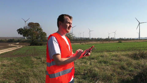 Technical engineer noting in tablet looking at wind turbine towers ビデオ