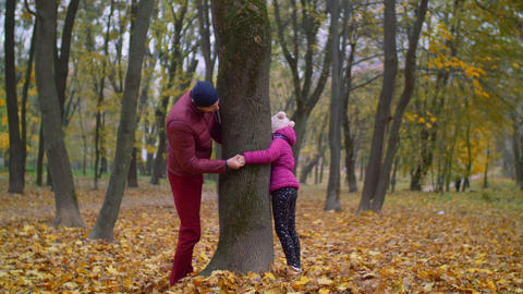 Joyful father and kid playing hide and seek in autumn GIF