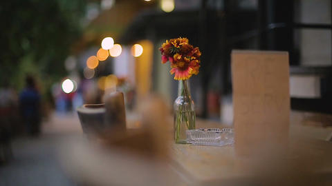 Bunch of flowers on reserved table in restaurant with outdoor seating, evening Live Action