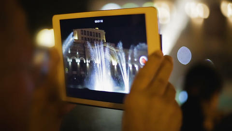 Tourist shooting video with portable device, Musical Fountains image on screen Live Action