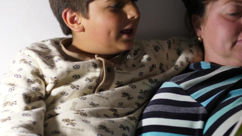 Blurred image of boy and his mother Reading book before the sleep Focusing on Footage