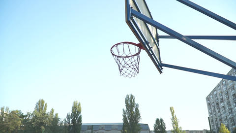 [alt video] Young guy throws a basketball into the basketball net