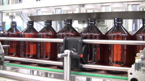 Process Of Bottle Filling, Close Up. A Machine Fills Bottles With Alcohol Live Action