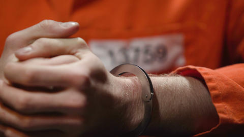 Anxious prisoner kneading fingers, regrets about committing crime, hands closeup Live Action