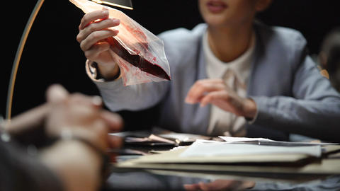 Female prosecutor showing knife with blood to suspect, waiting for confession Live Action