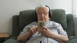 Old lady is listening music on a smartphone Live Action