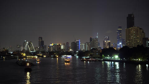 Lights of modern buildings in night downtown on skyline, and boats sailing along GIF
