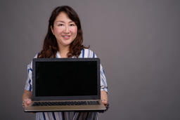 Asian businesswoman showing copy space from laptop computer Photo