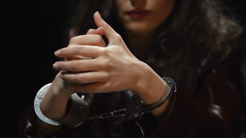 Impudent bored woman sitting in interrogation room, warming up wrists in cuffs Live Action