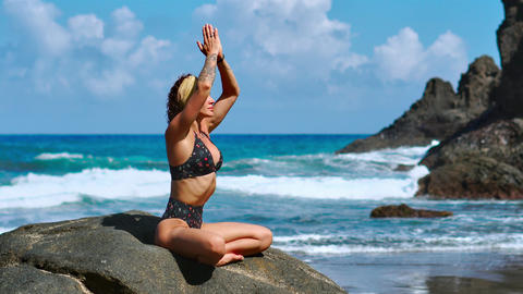 pretty blond girl in black top relaxes in yoga pose lotus on purple mat against Live Action