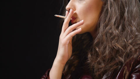 Attractive brunette smoking cigarette alone, bad habits among youth, close up Live Action