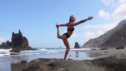 Girl doing yoga balancing on one leg standing on a stone. Peace of mind. Healthy Live Action