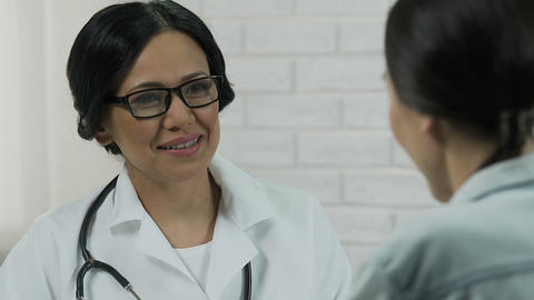 Friendly female physician telling good medical test results to patient, health Live Action