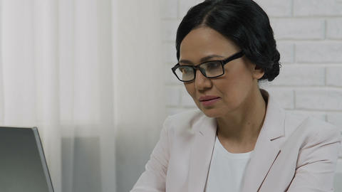 Attentive middle-aged lady boss reading report on laptop computer, career Footage