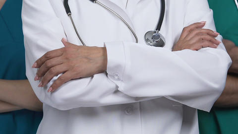 Close up of experienced medical staff with crossed hands posing before camera Live Action