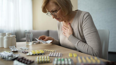 Sad woman looking at table full of pills and sighs, old age disease, addiction Footage