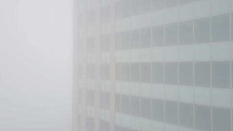 Aerial rising shot of office building in fog Footage