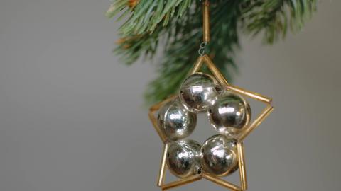 Original vintage ornament spinning while hanging on conifer branch. 4K resolution pedestal camera Live Action