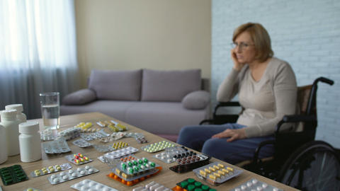 Female clinic patient sighs and looks at pills on the... Stock Video Footage