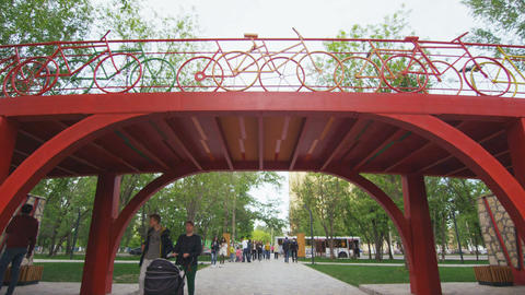 citizens walk along park under bridge with bicycle handrails Footage