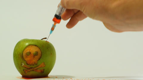syringe inserted into a green apple with an engraved skull, representative image Live Action