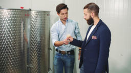 Men tasting fresh wine during production Footage