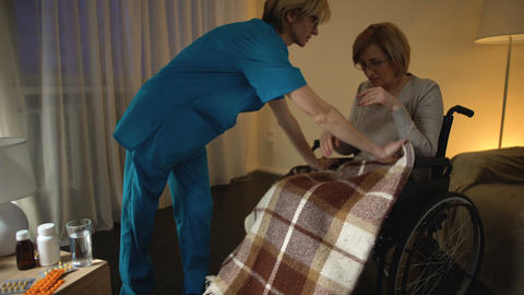 Nurse covering old woman in wheel chair with blanket, assistance and help Footage