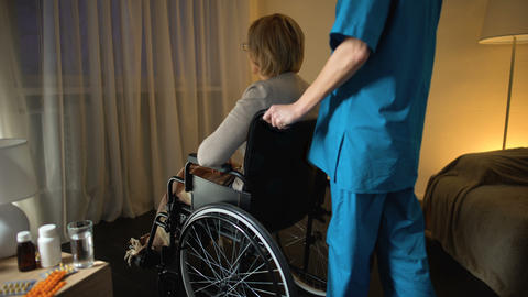 Medical worker bringing depressed old woman in wheelchair to room, loneliness Footage