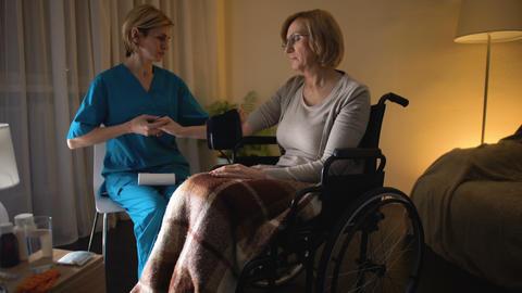 Female nurse measuring woman blood pressure, hypertension, old age hopelessness Footage
