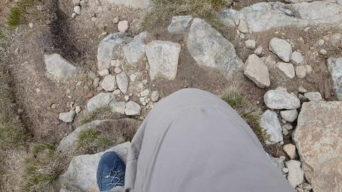 Footsteps of the man that goes down from the mountain in slow motion Footage